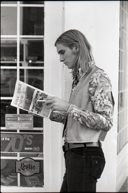 Tom Frank, standing on a corner, reading a copy of Free Spirit Press (vol. 1, 4) (Greenfield, Mass.), linking to the digital object