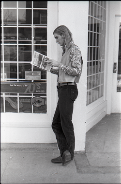 Tom Frank standing on a corner, reading a copy of Free Spirit Press (vol. 1, 4) (Greenfield, Mass.), linking to the digital object