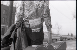 Tom Frank walking away from the camera, carrying a guitar case and a copy of Free Spirit Press (vol. 1, 4) in his rear pocket (Greenfield, Mass.), linking to the digital object