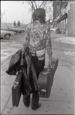 Tom Frank walking away from the camera and carrying a guitar case, a copy of Free Spirit Press (vol. 1, 4) in his rear pocket (Greenfield, Mass.), linking to the digital object