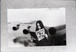 Heidi Bushell reading a copy of Free Spirit Press (vol. 1, 4) at the airport: manipulated copy print inserting image of airport in background , linking to the digital object
