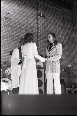 Wedding of Jim and Anne Baker: exchanging vows in front of minister and drum set (Turners Falls, Mass.), linking to the digital object