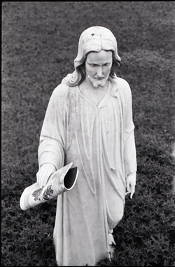 Statue of Jesus, copy of Free Spirit Press magazine set in his hand (New York, N.Y.), linking to the digital object