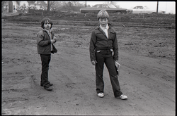 Two boys standing in a muddy lot (New York, N.Y.), linking to the digital object