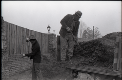 Two men with pitchforks, spreading mulch from the back of a truck (New York, N.Y.), linking to the digital object