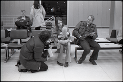 Richard Safft talking with family in waiting area at JFK airport (New York, N.Y.), linking to the digital object