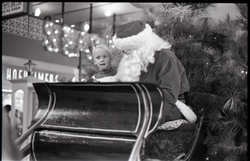 Santa Claus in his sleigh with child at the shopping plaza, JFK airport (New York, N.Y.), linking to the digital object