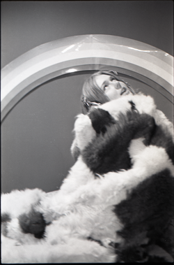 Lynn Smith wrapped in faux fur blanket, modeling Koss headphones (Turners Falls, Mass.), linking to the digital object