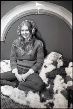 Lynn Smith sitting on faux fur blanket, modeling Koss headphones (Turners Falls, Mass.), linking to the digital object