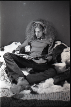 Richie Miller lolling on a faux fur blanket, modeling Koss headphones (Turners Falls, Mass.), linking to the digital object