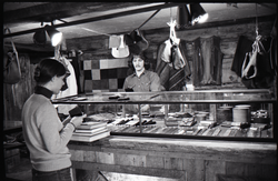 Don Muller with customer at the counter in the Leather Shed (Amherst, Mass.), linking to the digital object