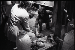 Don Muller (kneeling) and unidentified man near pottery display, the Leather Shed (Amherst, Mass.), linking to the digital object