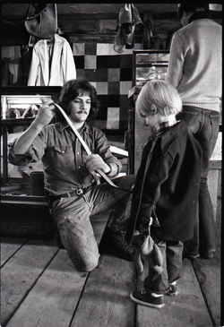 Don Muller kneeling fit a child with a belt, the Leather Shed (Amherst, Mass.), linking to the digital object