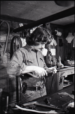Don Muller punching holes in leather strap, the Leather Shed (Amherst, Mass.), linking to the digital object