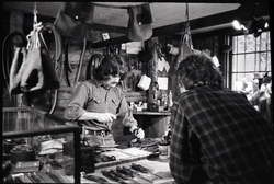 Don Muller working leather at his bench as a customer looks on, the Leather Shed (Amherst, Mass.), linking to the digital object