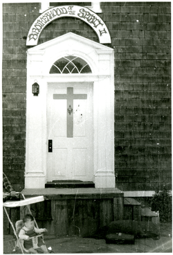 View of the doorway (with sign) to a Brotherhood of the Spirit house on Main Street (Northfield, Mass.), linking to the digital object