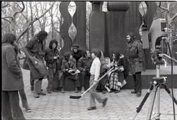 Kid with hockey stick walking past Richard Safft (reading) and other commune members during interview by Channel 5 news (New York, N.Y.), linking to the digital object
