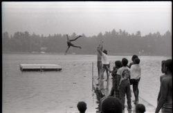 Group of summer campers (?) tossing a child into a lake, one onlooker wearing a Spirit in Flesh t-shirt, linking to the digital object
