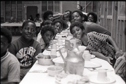 Inner City Round Table of Youth campers: group of Campers at dining table, one wearing a Spirit in Flesh t-shirt, linking to the digital object