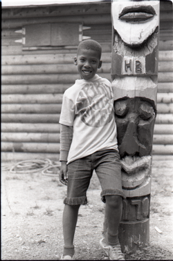 "Young boy in Spirit in Flesh t-shirt, posed next to ""totem pole"" at summer camp, linking to the digital object"
