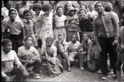 Inner City Round Table of Youth campers: group of children at summer camp, some wearing Spirit in Flesh t-shirts, posed in front of camp building, linking to the digital object