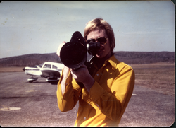 James Baker with video camera, airplane in background (Turners Falls, Mass.), linking to the digital object