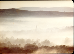 View of New England hills in the mist, a church steeple climbing through (Turners Falls, Mass.), linking to the digital object