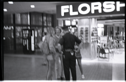 Free Spirit Press crew members talking with police office in an indoor mall (Springfield, Mass.), linking to the digital object