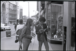 Free Spirit Press crew member (Charlie Ribokas) and young man looking at copy of the magazine on a street (Springfield, Mass.), linking to the digital object