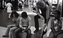 Commune member distributing Free Spirit Press in an indoor shopping mall: communard with group seated in center of the mall (Springfield, Mass.), linking to the digital object