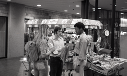 Commune member distributing Free Spirit Press in an indoor shopping mall: communards next to a fruit vendor (Springfield, Mass.), linking to the digital object
