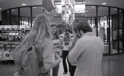 Commune member distributing Free Spirit Press in an indoor shopping mall: self-portrait of photographer photographing a group talking about the magazine (Springfield, Mass.), linking to the digital object