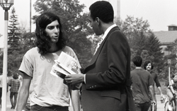 Bill Grabin showing Free Spirit Press magazine to faculty member in front of the UMass Amherst Student Union (Amherst, Mass.), linking to the digital object