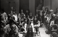 UMass Amherst students in a lecture hall, some seated on the floor (Amherst, Mass.), linking to the digital object