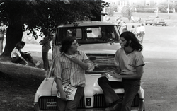 Bill Grabin, with pile of Free Spirit Press magazine, talking with UMass Amherst student sitting on the hood of a 1968 Mercury Cougar (Amherst, Mass.), linking to the digital object