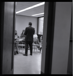 View through an open door of a class is session, UMass Amherst (Amherst, Mass.), linking to the digital object