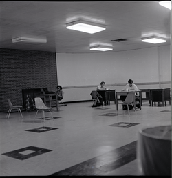 Students studying in barren room in the UMass Amherst Student Union Building (Amherst, Mass.), linking to the digital object