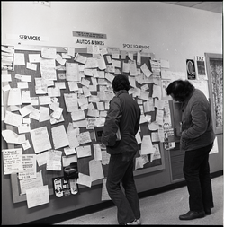 Students looking at a bulletin board in the UMass Amherst Student Union Building (Amherst, Mass.), linking to the digital object