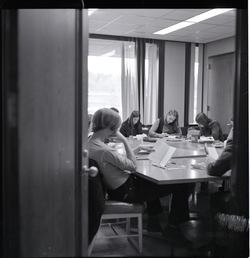 UMass Amherst students sitting around a classroom table, reading (Amherst, Mass.), linking to the digital object