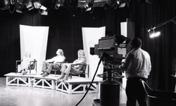 Commune members at the WGBY Catch 44 (public access television) interview: cameraman filming Anne Baker, James Baker, and Bruce Geisler on stage (Springfield, Mass.), linking to the digital object
