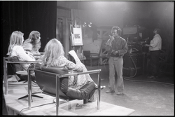 Commune members at the WGBY Catch 44 (public access television) interview: shot from the rear of Jim Baker, Bruce Geisler, and Anne Baker (l. to r.) on stage (Springfield, Mass.), linking to the digital object