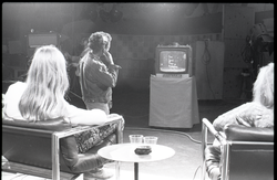 "Commune members at the WGBY Catch 44 (public access television) interview: shot from the rear of Anne and Jim Baker on stage, looking at monitor showing title for ""Free Spirit Press publishing"" (Springfield, Mass.), linking to the digital object"