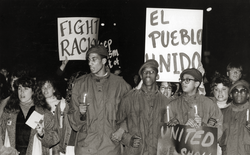"Night rally with placards reading ""Fight racism"" and ""El Pueblo Unido"", linking to the digital object"