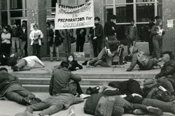 "Staged die-in beneath banner reading ""Preparation for nuclear war is preparation for suicide"", linking to the digital object"