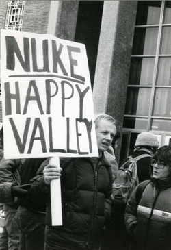 "Protester with placed reading ""Nuke Happy Valley"", linking to the digital object"