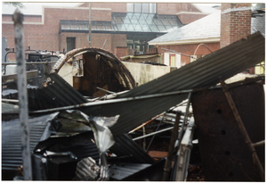 dismantled parts to the back room of Munson Annex are piled up by the quonset hut