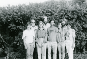 Group standing in front of greenery, Robert Houriet (four from left) and Stewart Hoyt and Grace Gershuny (far left)