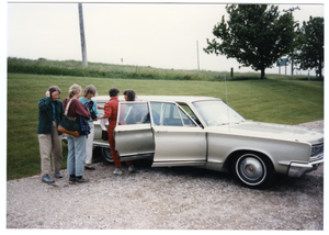 Group of women standing a station wagon