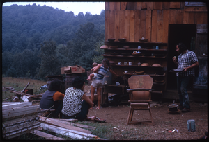 Johnson Pasture Commune: Group, infant, outside house, linking to the digital object