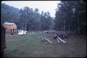 Johnson Pasture Commune: Lumber stacked in front of house, Volkswagen beetle, linking to the digital object